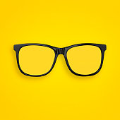 Minimal concept of  transparent glasses flat lay on pastel yellow, orange color paper background. Top view. Copy space