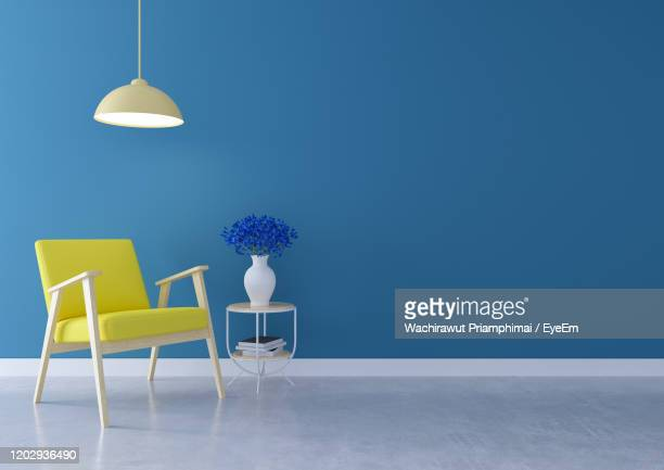 minimal interior of living room, yellow sofa with  lamp on concrete flooring and white blue wall - ubicaciones geográficas fotografías e imágenes de stock