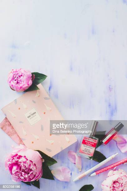 Minimal styled flat lay with peony flowers, petals, stationery and notebooks on a white background