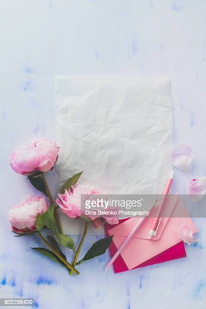Minimal styled flat lay with peony flowers, petals, stationery and notebooks on a pastel background with copy space