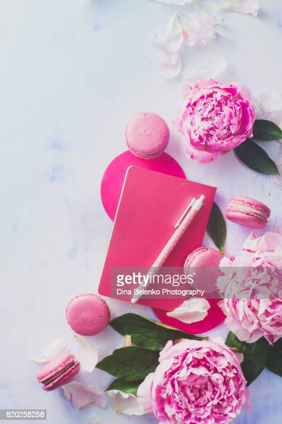 Minimal styled flat lay with peony flowers with petals, stationery and notebooks on a pastel background
