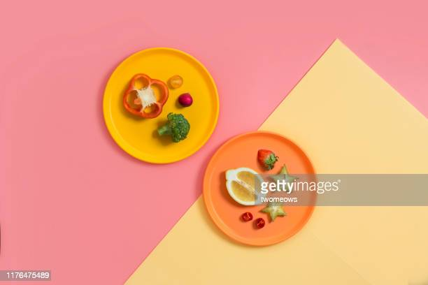 minimalist colourful vegetables and fruits still life. - plate stock pictures, royalty-free photos & images