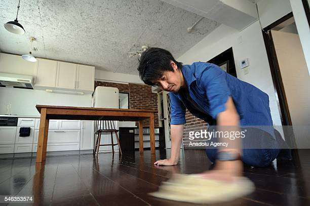 Minimalist Naoki Numahata cleans the floor of his home in Tokyo Japan on July 02 2016 Naoki Numahata a freelance writer who lives with his wife and...
