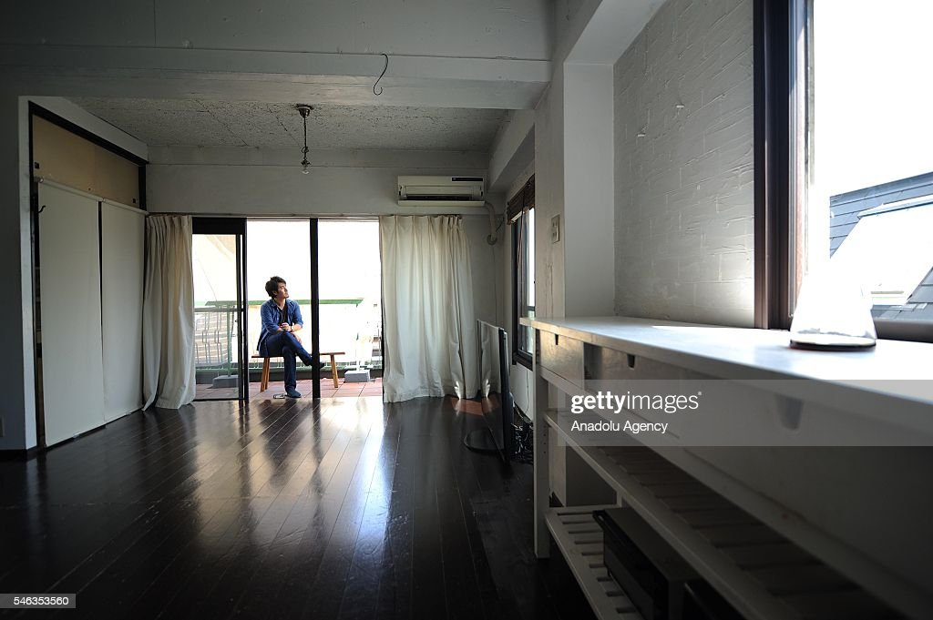 Minimalist Naoki Numahata is seen sitting in his balcony at his apartment in Tokyo, Japan, on July 02, 2016. Naoki Numahata, 41, a freelance writer who lives with his wife and their daughter, decided to live less cluttered with useless personal and domestic possessions during a travel and after meeting a family who live quite simply in Croatia. This philosophy 'Minimalism' has become famous in recent years in Japan especially between young people who want nothing to do with acquiring material possessions, but would rather spend their money, time, and effort on things that they truly enjoy. Minimalism is a different style that uses pared-down design elements. Minimalism in the arts began in postWorld War II Western art, most strongly with American visual arts in the 1960s and early 1970s.