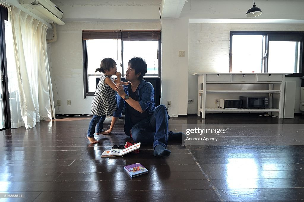 Minimalist Naoki Numahata talks to his three-years-old daughter Ei in the center of the living at their home in Tokyo, Japan, on July 02, 2016. Naoki Numahata, 41, a freelance writer who lives with his wife and their daughter, decided to live less cluttered with useless personal and domestic possessions during a travel and after meeting a family who live quite simply in Croatia. This philosophy 'Minimalism' has become famous in recent years in Japan especially between young people who want nothing to do with acquiring material possessions, but would rather spend their money, time, and effort on things that they truly enjoy. Minimalism is a different style that uses pared-down design elements. Minimalism in the arts began in postWorld War II Western art, most strongly with American visual arts in the 1960s and early 1970s.