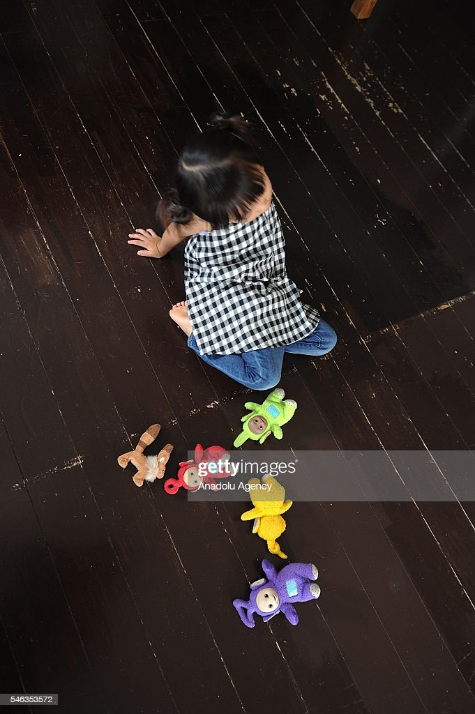 Minimalist Naoki Numahatas daughter Ei plays with dolls on the floor of the family's living-room in Tokyo, Japan, on July 02, 2016. Naoki Numahata, 41, a freelance writer who lives with his wife and their daughter, decided to live less cluttered with useless personal and domestic possessions during a travel and after meeting a family who live quite simply in Croatia. This philosophy 'Minimalism' has become famous in recent years in Japan especially between young people who want nothing to do with acquiring material possessions, but would rather spend their money, time, and effort on things that they truly enjoy. Minimalism is a different style that uses pared-down design elements. Minimalism in the arts began in postWorld War II Western art, most strongly with American visual arts in the 1960s and early 1970s.