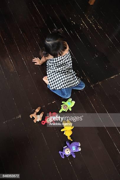 Minimalist Naoki Numahatas daughter Ei plays with dolls on the floor of the family's livingroom in Tokyo Japan on July 02 2016 Naoki Numahata a...