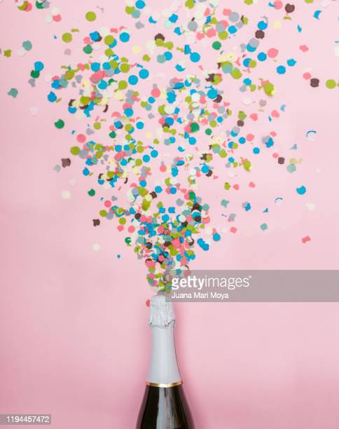 minimalist photograph of a bottle of champagne, confetti comes out of it.  celebration and new year concept - 祝う ストックフォトと画像