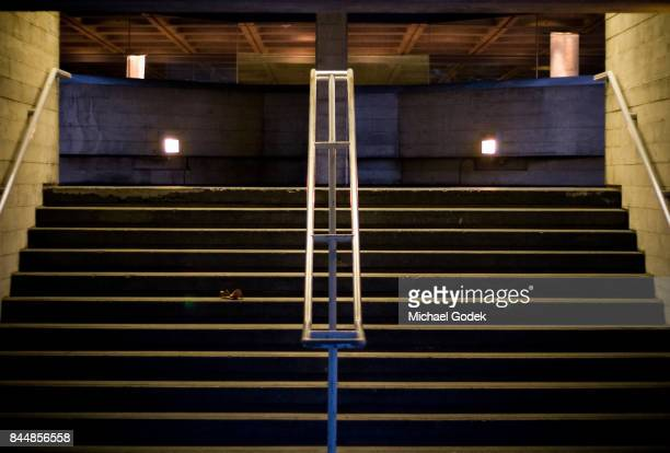 Minimalist shot of symmetrical staircase at night with a single leaf breaking up the repetition