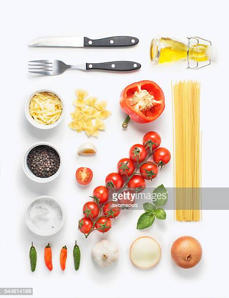 Minimalist style flat lay pasta recipe ingredient and cutlery set on white background.