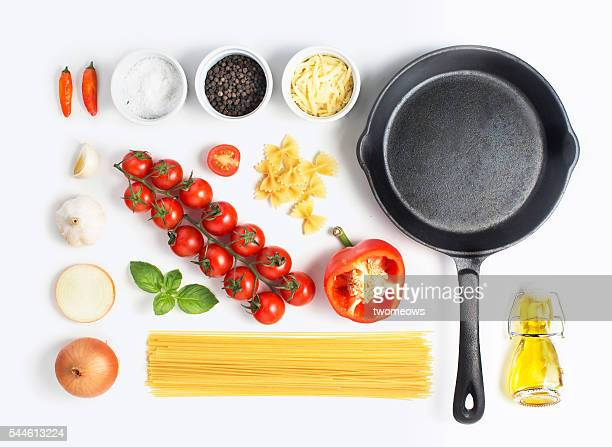 Minimalist style flat lay pasta recipe ingredient and metal cooking pan on white background.