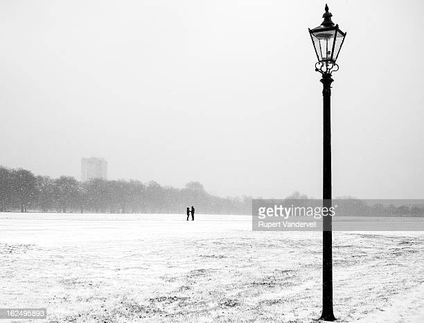 CONTENT] A minimalist winter scene set in the snowy landscape of Hyde Park London Two people in the distance hold hands and share an intimate moment...