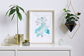 Minimalistic home interior floral poster mock up with vertical wooden photo frame, avocado plant, accessories and hanging plant in geometric pot on white wall background. Concept of white shelf.