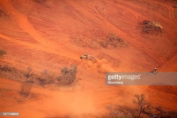 A mining truck and a bulldozer drive across dusty dirt tracks at the Mutanda copper and cobalt mine in Mutanda Katanga province Democratic Republic...
