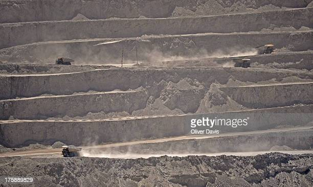 Mining trucks and excavated layers of rock in a deep open-pit mine. Chuquicamata is the largest open-pit copper mine in the world, located on the...