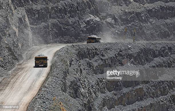 Mining trucks ferry diamondbearing kimberlite rock away from the excavation area of Jwaneng mine operated by the Debswana Diamond Co a joint venture...