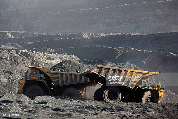 Mining trucks manufactured by Komatsu Ltd transport excavated rocks from the open pit to a dump at the Neryungrinsky coking coal mine operated by OAO...