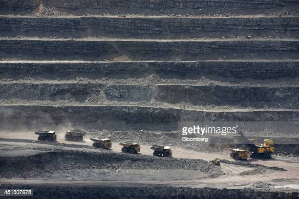Mining trucks operate in the open pit during the excavation of coking coal at the Neryungrinsky mine operated by OAO Mechel in Neryungri Sakha...
