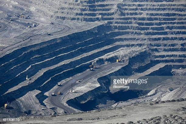 Mining trucks operate on different levels in the open pit of the Neryungrinsky mine for coking coal operated by OAO Mechel in this aerial view in...