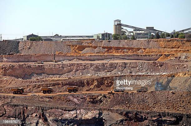 Mining trucks wait to collect excavated rock on a pit road beneath the main kimberlite rock processing facility at the Jwaneng mine operated by the...