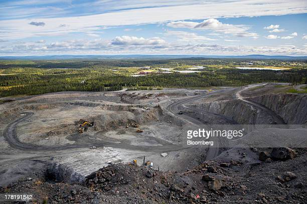 Mining vehicles and excavators operate in the pit of the open cast iron ore mine run by LKAB Sweden's stateowned mining company in Svappavaara near...