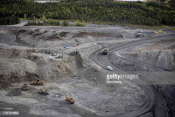 Mining vehicles operate in the pit of the open cast iron ore mine run by LKAB Sweden's stateowned mining company in Svappavaara near Kiruna Sweden on...
