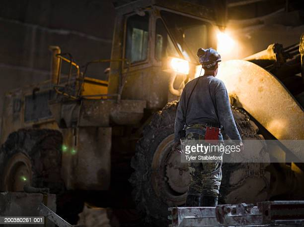 Mining worker looking at excavation vehicle in quarry, rear view