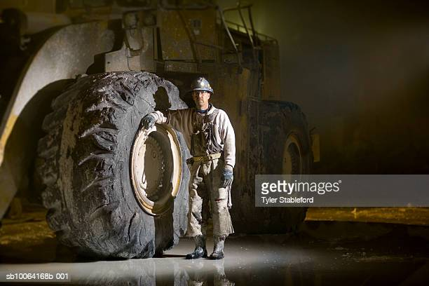 Mining worker standing beside tyre in marble quarry