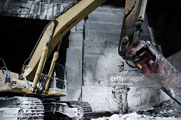 Mining worker standing near large machine, portrait