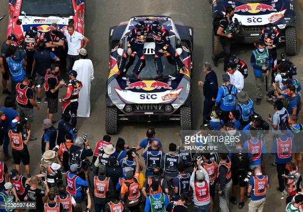 Mini's driver Stephane Peterhansel and his co-driver Edouard Boulanger of France celebrate their victory after winning the Dakar Rally 2021, at the...