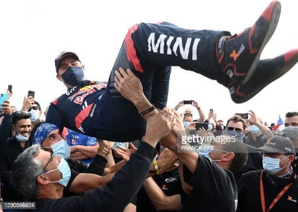 Mini's driver Stephane Peterhansel celebrates with teammates their victory after winning the Dakar Rally 2021, at the end of the last stage between...
