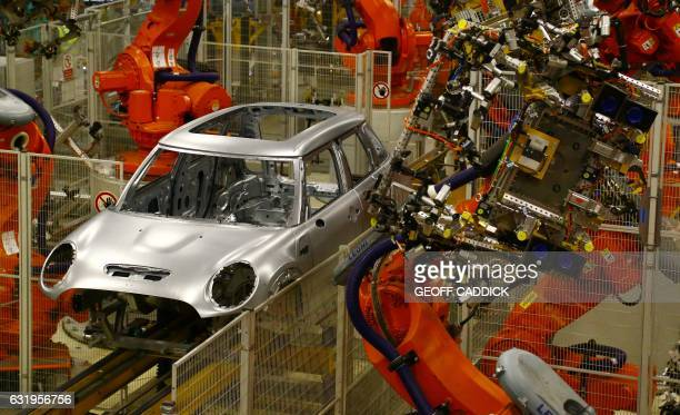 Minis in the 'Body in white' stage of manufacture pass along a robotic assembly line at the BMW Mini car production plant in Oxford west of London on...