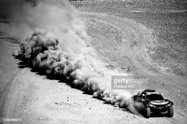 Mini's Spanish driver Carlos Sainz and co-driver Lucas Cruz compete during Stage 1 of the 2021 Dakar Rally between Jeddah and Bisha in Saudi Arabia,...