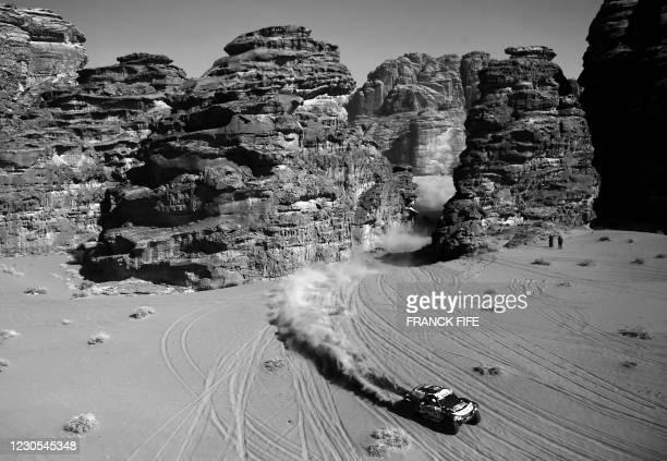 Mini's Spanish driver Carlos Sainz and co-driver Lucas Cruz compete during stage 8 of the Dakar Rally 2021 between Sakaka and Neom, in Saudi Arabia,...