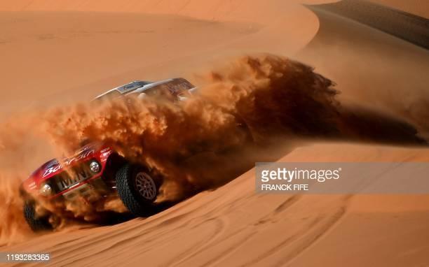 Mini's Spanish driver Carlos Sainz and co-driver Lucas Cruz compete in the Stage 7 of the Dakar 2020 between Riyadh and Wadi Al Dawasir, Saudi...