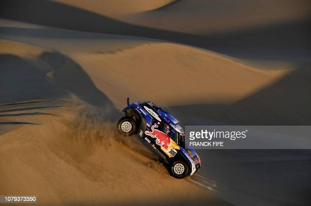 Mini's Spanish driver Carlos Sainz and co-driver Lucas Cruz compete during the Stage 2 of the Dakar 2019 between Pisco and San Juan de Marcona, Peru,...