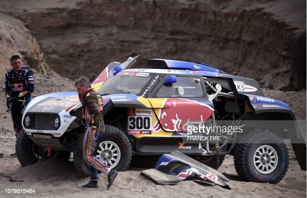 Mini's Spanish driver Carlos Sainz and codriver Lucas Cruz stand next to their car after the front suspension on their Mini broke during Stage 3 of...