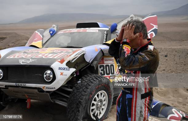 Mini's Spanish driver Carlos Sainz gestures next to his car after the front suspension on his Mini broke during the Stage 3 of the Dakar Rally...