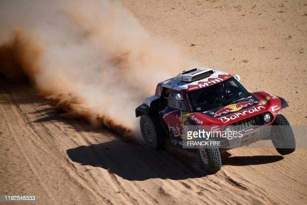 TOPSHOT Mini's Spanish drivers Carlos Sainz and codriver Lucas Cruz compete during the Stage 4 of the Dakar 2020 between Neom and AlUla Saudi Arabia...