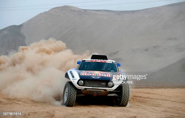 Mini's Spanish drivers Carlos Sainz of Spain and codriver Lucas Cruz of Spain take part in a driving session in San Bartolo 75 km south of Lima on...