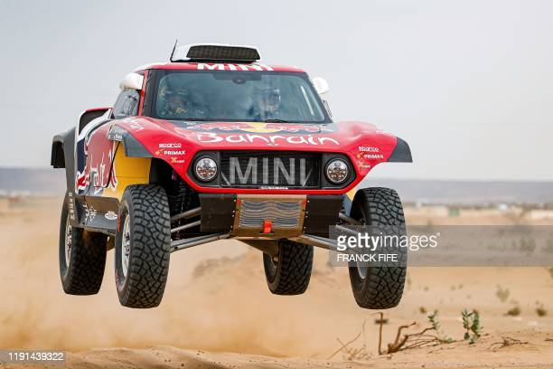 TOPSHOT Mini's Spanish drivers Carlos Sainz of Spain and codriver Lucas Cruz of Spain drives during a driving session on the eve of technical checkup...