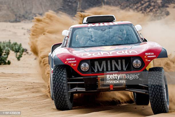 Mini's Spanish drivers Carlos Sainz of Spain and codriver Lucas Cruz of Spain steers their car during a driving session on the eve of technical...