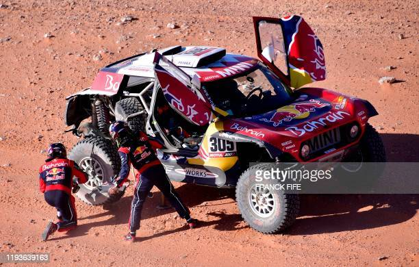 Mini's Spanish drivers Carlos Sainz of Spain and codriver Lucas Cruz of Spain repairs their car after a flat tire during the 2020 Rally Dakar Stage 9...