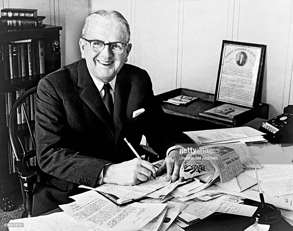 Minister and author Dr Norman Vincent Peale smiling and working at his desk, New York, New York, 1966.
