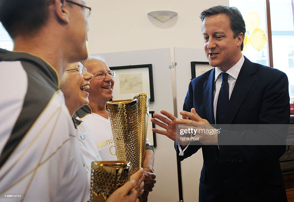 Minister David Cameron meets Olympic torchbearer during a visit to the region on August 01, 2012 in Coleraine, Northern Irland. During his time in Coleraine, Cameron visited the home club of one of the top British rowers, Alan Campbell, just ahead of his next stage in the Olympics semi-final race.