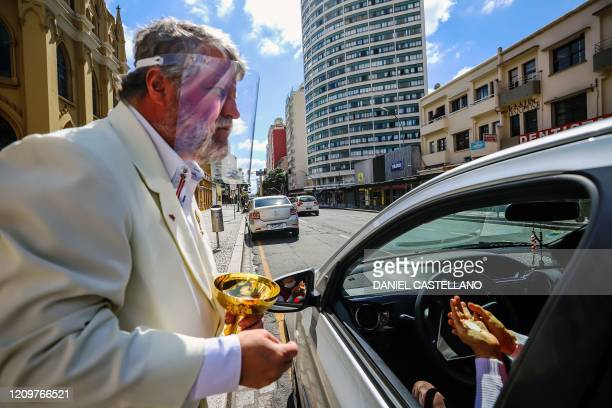 Minister Edilson Paes from the Basilica Cathedral wears a face shield as he gives communion in a drive through ceremony during an easter sunday...