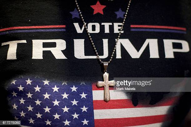 Minister EJ Christian wears a Donald J Trump themed shirt with a cross necklace before the Republican Presidential nominee holds an event at the...