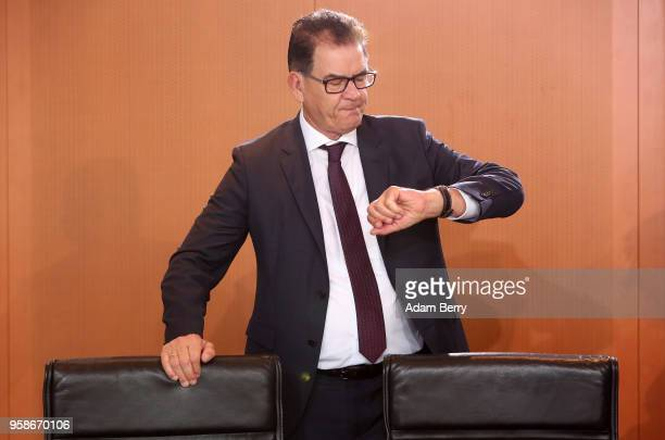 Minister for Economic Cooperation and Development Gerd Mueller looks at his watch as he arrives for the weekly German federal Cabinet meeting on May...