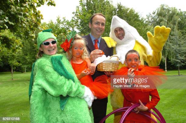Minister for Health and Children Micheal Martin holding a basket of strawberries with the Diebold Family Emily Jessica father Jonathon and Zachary...