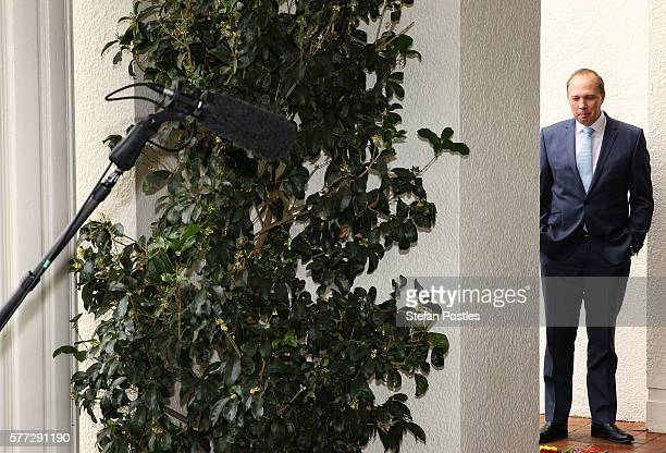 Minister for Immigration and Border Protection Peter Dutton stands on the sidelines after official photographs have been taken at the swearingin...